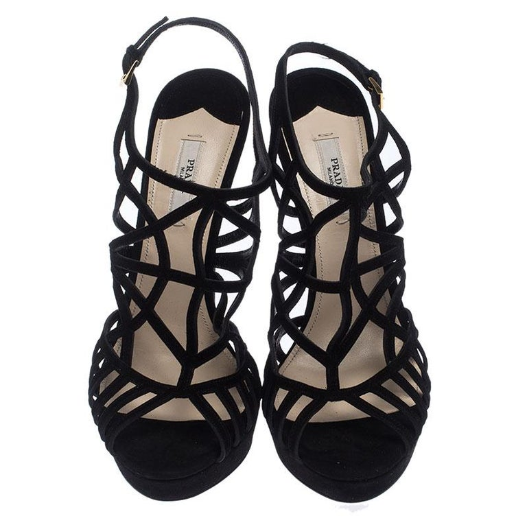 Look stunning in these luxurious sandals from Prada. The sandals are crafted from suede and feature open toes and a caged design, buckled ankle straps, and 13.5 cm stiletto heels. These black sandals are versatile and can be worn on any