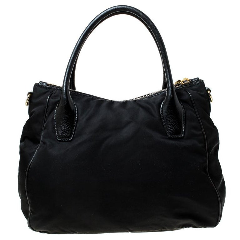When you carry this Prada creation, be ready to catch admiring glances as this bag is stylish and handy. The bag has been crafted from Tessuto nylon and leather trims in a lovely black shade and equipped with two top handles and gold-tone logo