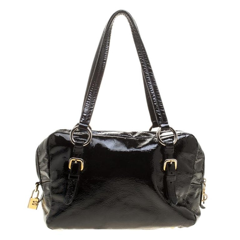 Made from black patent leather with a textured feel, this satchel by Prada will carry all your essentials in style. The bag features an ID tag and a combination padlock in gold-tone. The spacious interior is lined with nylon and secured by a zip