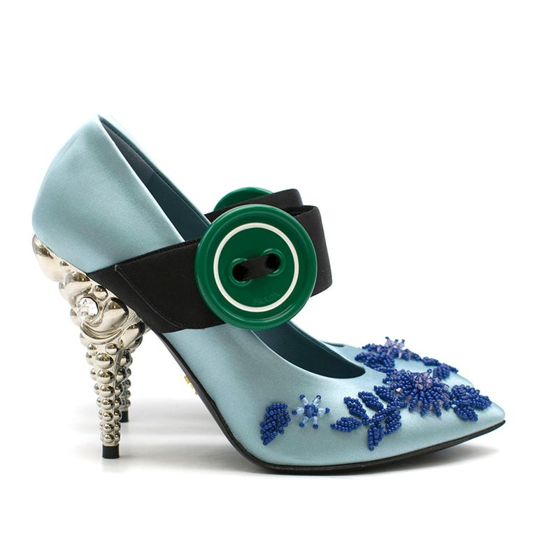 Prada Blue Bead-embellished Satin Pump  - Blue satin pump - Pointed toe - Front bead embellishment  - Front black strap with oversized green button - Silver-tone 3-D decorative high heel, clear crystal embellished  - Blue leather lining with logo