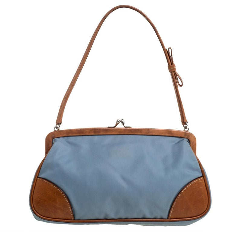 This stylish pochette bag by Prada is great for parties. Crafted from blue & brown nylon & leather, it has a frame that adds interest. The strap closure carries the brand logo. It has a nylon interior, a single handle, and silver-tone hardware
