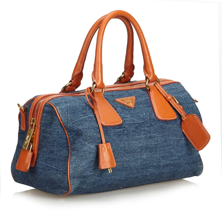 66ce81e08b52 This satchel features a denim body with saffiano leather trim, rolled  leather handles, top