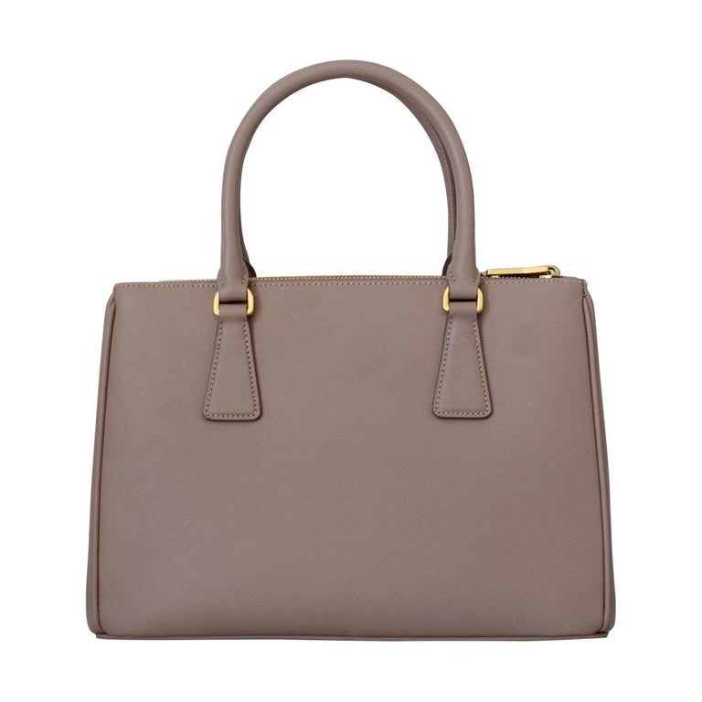 Fantastic and brand new Prada Galleria Saffiano leather Cameo color Two leather handles Detachable adjustable shoulder strap Gold-finish hardware Debossed lettering logo on leather triangle Snap closure on sides Two outside pockets with zipper
