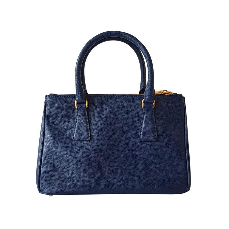 Fantastic and brand new Prada Galleria Saffiano leather Two leather handles Detachable adjustable shoulder strap Gold-finish hardware Debossed lettering logo on leather triangle Snap closure on sides Two outside pockets with zipper closure Three