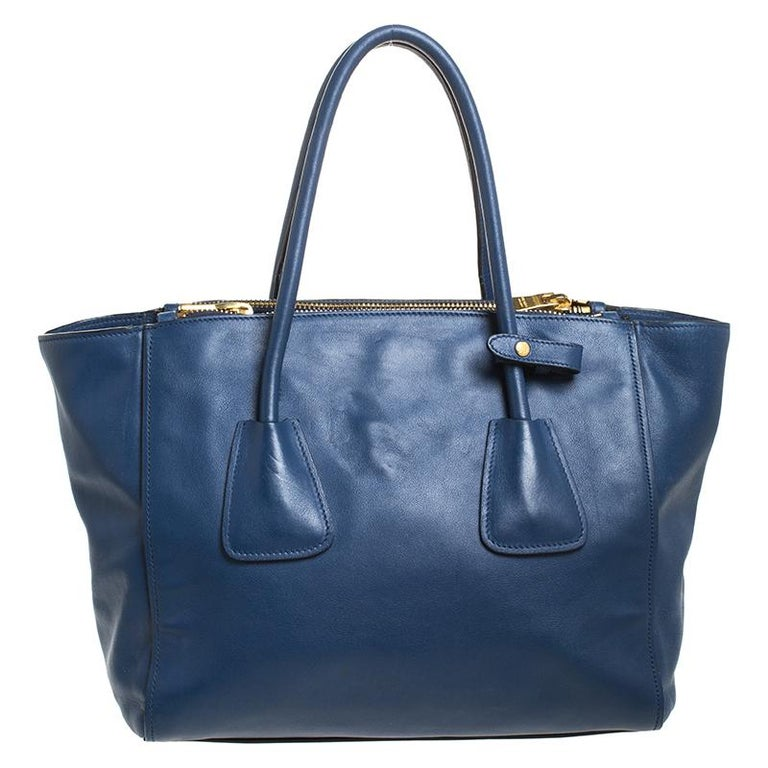 Add some effortless style and luxury to your everyday looks with this stunning Prada Twin tote. Crafted in Italy, it is made of blue Glace leather and has a lovely silhouette. It has a zip closure that leads to a nylon-lined interior with a zip