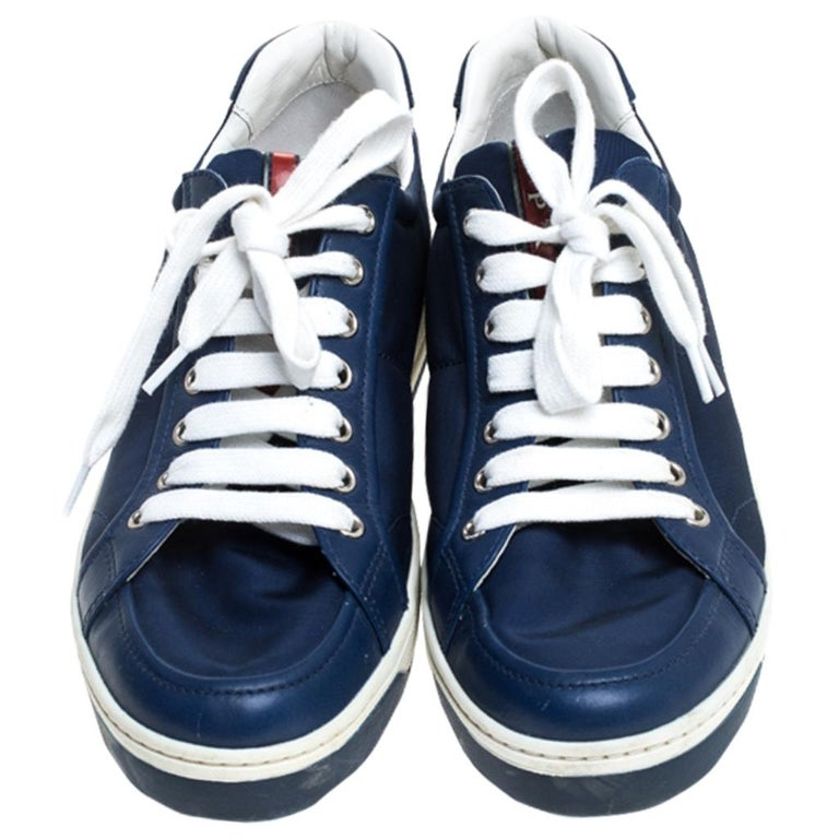 Fall in love with casual wear every time you step out in these sneakers from Prada. They've been crafted from blue leather and fabric and are styled with laces on the vamps. The sneakers are filled with comfort and effortless style.  Includes: