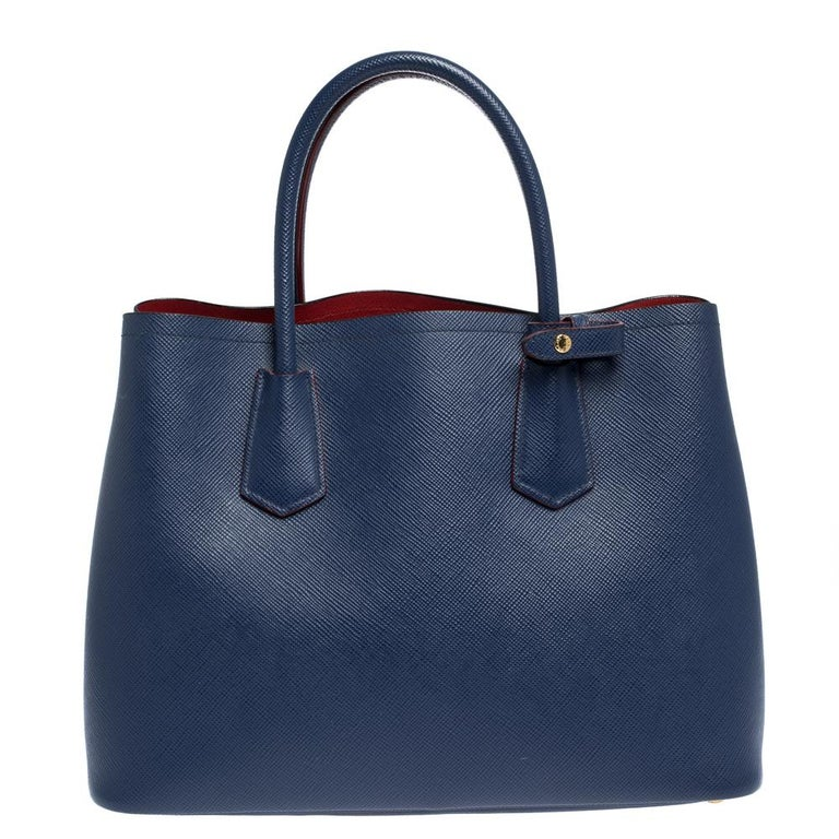 This lovely tote from Prada is crafted from Saffiano Cuir leather and features a blue shade. It flaunts dual handles, brand logo, protective metal feet, and a spacious leather-lined interior with enough space to house all your belongings. It is