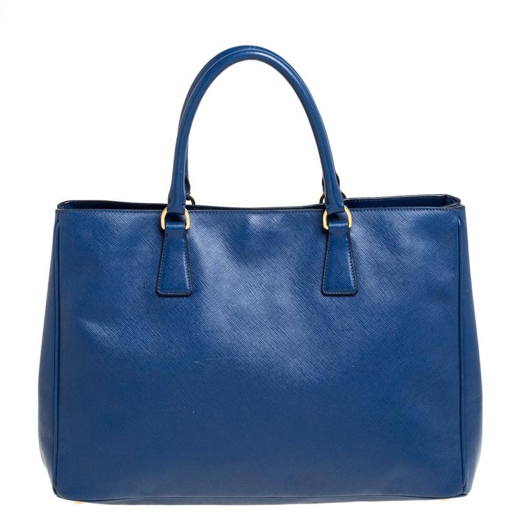 Bringing a mix of timeless fashion and fine craftsmanship is this large tote from Prada. The bag comes crafted from Saffiano Lux leather and designed with two handles, gold-tone hardware, and a capacious interior. Signature elements complete the
