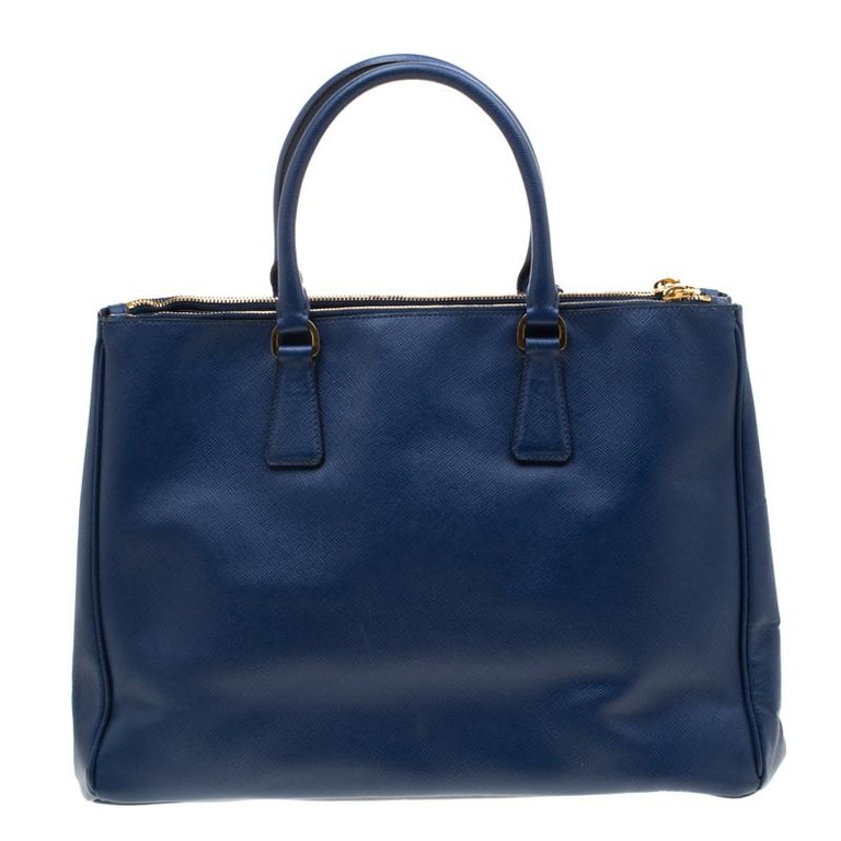 Feminine in shape and grand on design, this Double Zip tote by Prada will be a loved addition to your closet. It has been crafted from the signature Saffiano Lux leather and styled minimally with gold-tone hardware. It comes with two top handles,