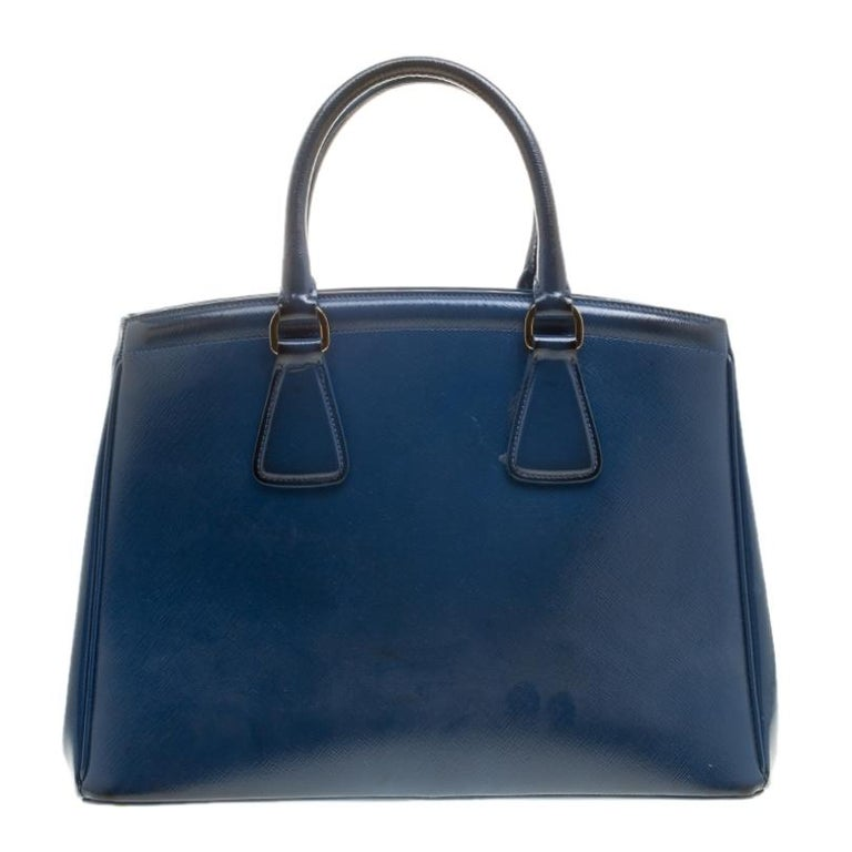 Masterfully created, this Prada tote is a style icon. Designed in a leather body, it exudes style, class and dignity in equal measures. This delightful blue piece is held by two top handles and equipped with a spacious nylon interior.  Includes: The