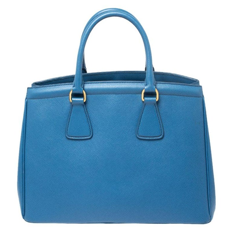 Masterfully created, this Prada tote is a style icon. Designed in a Saffiano Lux leather body, it exudes style and class in equal measures. This delightful blue piece is held by two top handles and equipped with a spacious nylon interior.  Includes: