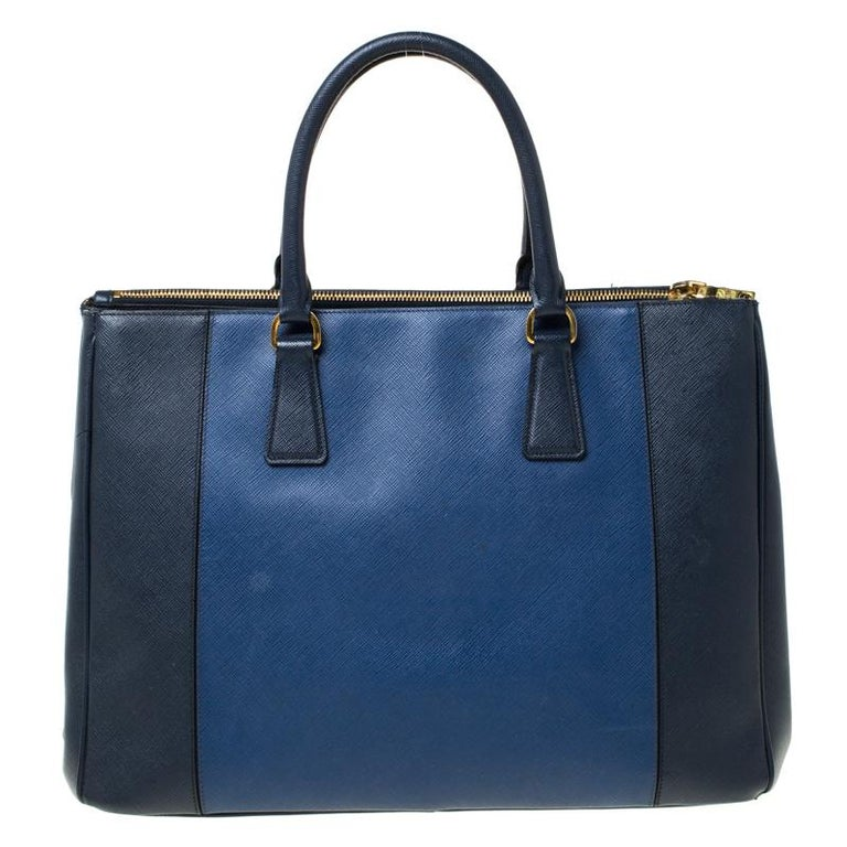 Feminine in shape and grand on design, this Double Zip tote by Prada will be a loved addition to your closet. It has been crafted from two-toned Saffiano Lux leather and styled minimally with gold-tone hardware. It comes with two top handles, two