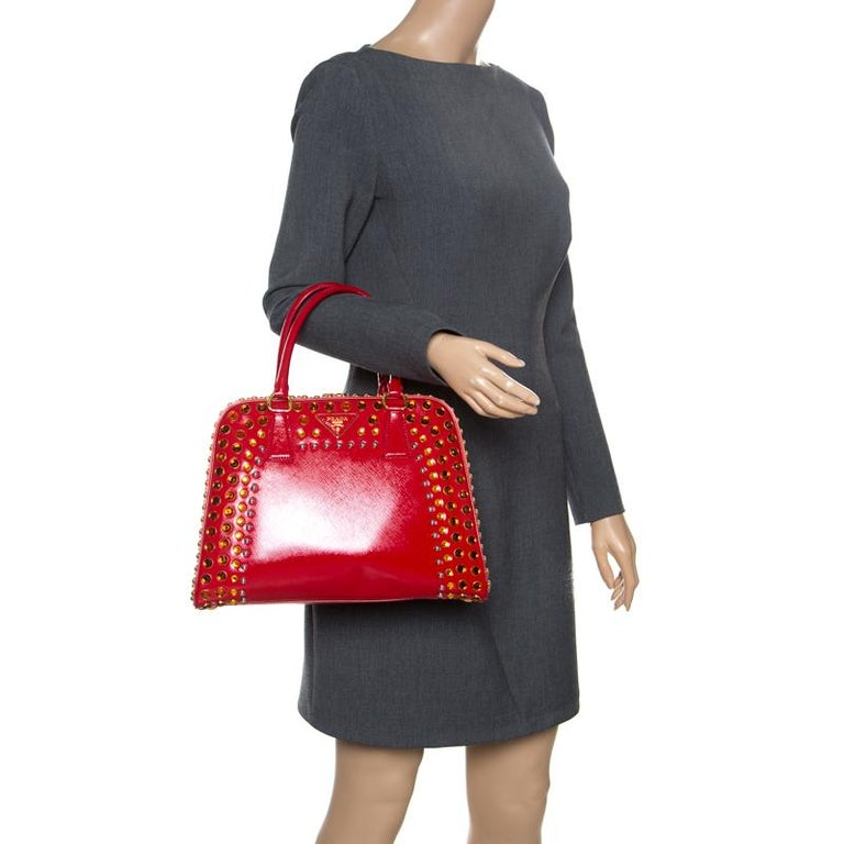 Giving handle bags an elegant update, this Pyramid Frame bag by Prada will be a valuable addition to your closet. It has been crafted from patent leather and styled with shimmery embellishments. It comes with dual top handles, protective metal feet