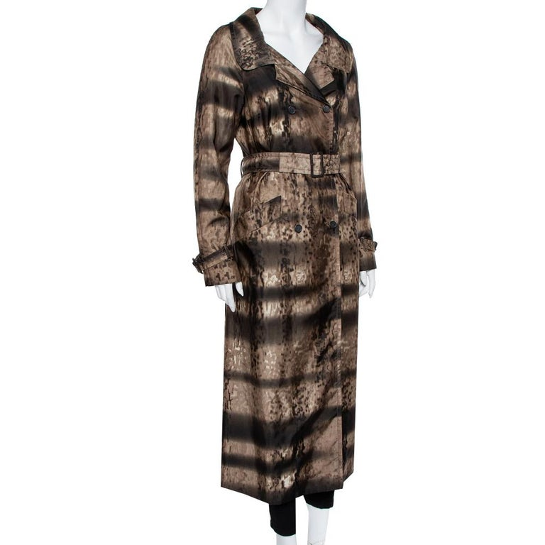 This Prada double-breasted, synthetic brown animal-printed trench coat is a chic, stylish cover-up with a collared neck, a detachable belt, two hip pockets, and front button closure. It is a lightweight creation offering a comfortable fit.