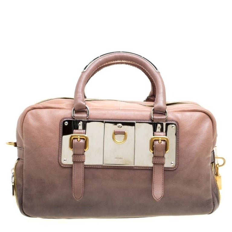 This elegant Bauletto bag from Prada is crafted from leather and is perfect for your fashionable outings. The bag features splendid details in the form of the dual round handles, gold-tone lock closure, and zip detailing at the bottom. The top zip