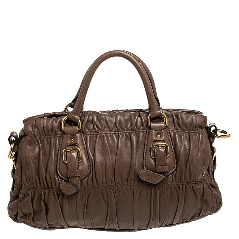 Prada brings you this lovely satchel that has been crafted from gathered leather in a brown hue. It has a well-sized nylon interior and the bag is complete with two top handles. Stylish and ideal for daily use, this bag is a worthy buy.  Includes: