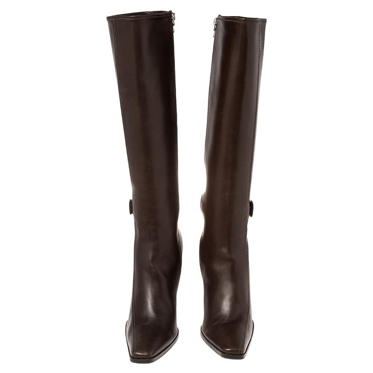 It's time to rock all your outings with these chic and smart knee-length boots from Prada. Exuding oodles of style, these brown leather boots are designed with square toes, silver-tone buckle details, and side zippers. They are endowed with