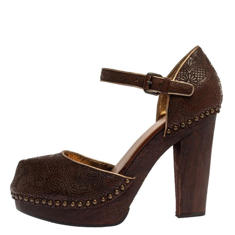Add vintage charm to your overall look with these sandals from the house of Prada. Crafted in Italy, they are made from intricately embroidered leather in a brown shade and outlined with metal studs. These sandals have 11.5 cm wooden block heels