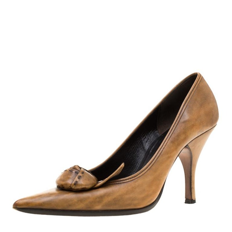 It would be a great choice to go for this well-cut, stylish pumps from the house of Prada. Ensure that your outfit looks lively by pairing up it with these brown pumps. They are made from leather in and designed with flower details and 10 cm