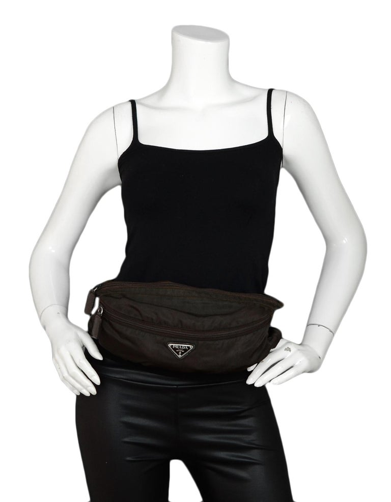 Prada Brown Nylon Zip Front Waist Bag/Fanny Pack   Color: Brown Hardware: Silvertone hardware Materials: Nylon Lining: Brown textile lining Closure/Opening: Front zip Exterior Pockets: One zipper pocket Interior Pockets: N/A Exterior Condition: Good