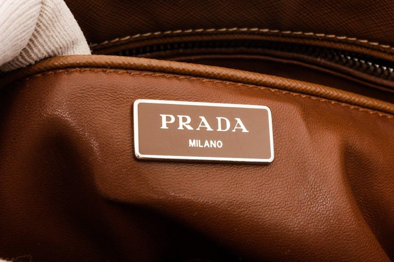 Prada Brown Saffiano Leather Double Zip Tote Bag with gold-tone hardware, three interior compartments pockets, dual top handles, leather shoulder strap, and closure.  26187MSC