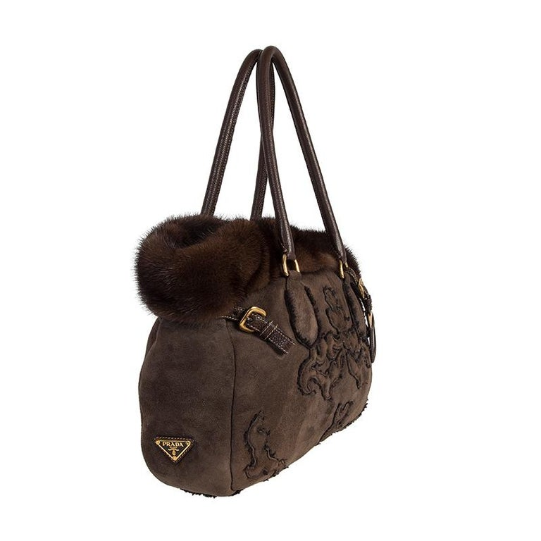 Prada toe bag in brown shearling with brown mink trim. Opens with a magnetic snap closure. Lined in dark brown shearling wool. The exterior features a ornate design with leather details and handles. Has been carried and is in excellent