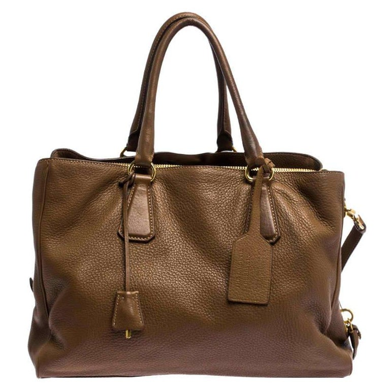 This elegant tote from Prada is crafted from soft leather and is perfect for daily use. It comes in a stunning shade of brown. The bag features double handles, protective metal feet, and a removable shoulder strap. It has a top-zip closure that