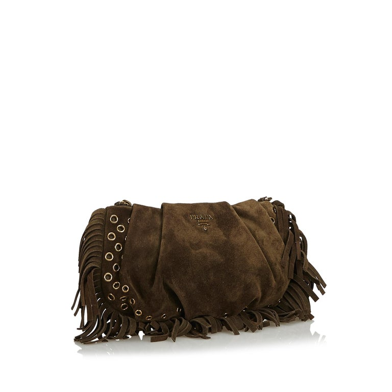 This clutch bag features a suede body with metal accents and fringe details, a top zip closure, and an interior zip pocket. It carries as B+ condition rating.  Inclusions:  Box Authenticity Card  Dimensions: Length: 14.00 cm Width: 24.00 cm Depth: