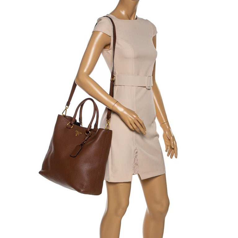 This leather shopper tote from Prada has been fabulously designed in a smart silhouette with the brand label in gold-tone at the front. It comes with a nylon-lined interior. This tote is held by two top handles and a shoulder strap and is