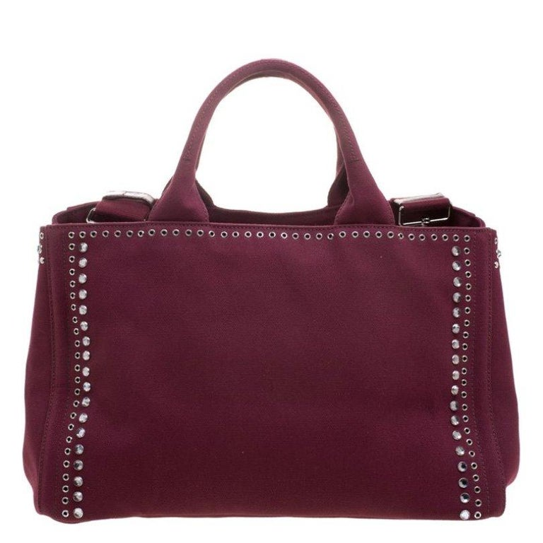High on appeal and style, this Gardener's tote is a Prada creation. It has been crafted from burgundy canvas and shaped to exude class and luxury. The bag comes with two handles, a shoulder strap, protective metal feet, and studs and crystal