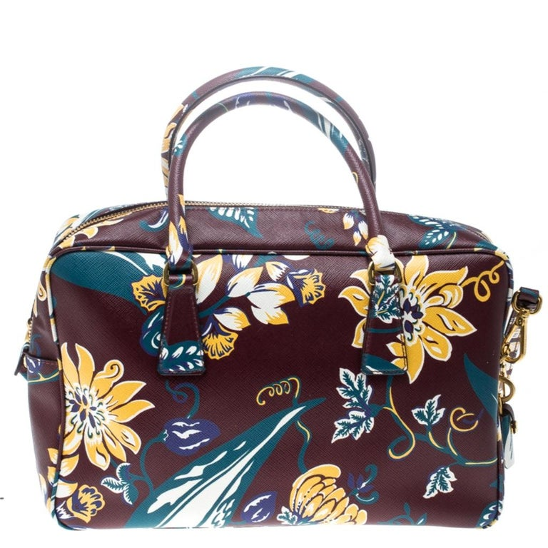 This elegant Bauletto bag from Prada is crafted from Saffiano leather and is perfect for your fashionable outings. The beautiful burgundy colour is ravishing. The bag features splendid details in the form of the multicolour floral print all over,