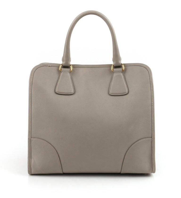 "PRADA c.2011 ""Saffiano Lux"" Pomice Grey Leather Tote + Strap Large Handbag  Estimated Retail: $2390   Brand / Manufacturer: Prada Manufacturer Style Name: Saffiano Lux Style: Handbag, shoulderbag, top handle bag, tote Color(s): Pomice Lined:"