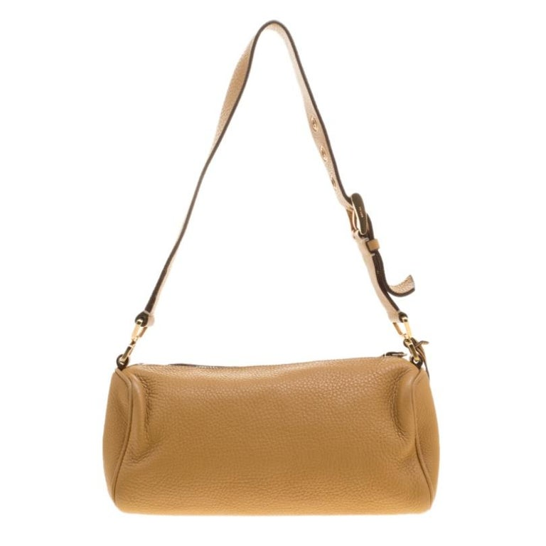 The smooth and subtle hue of this bag will blend perfectly with any dress of your pick. Get your hands on this beautiful leather shoulder bag to nail a picture perfect look. It is from Prada and it is designed with a shoulder strap and a zipper