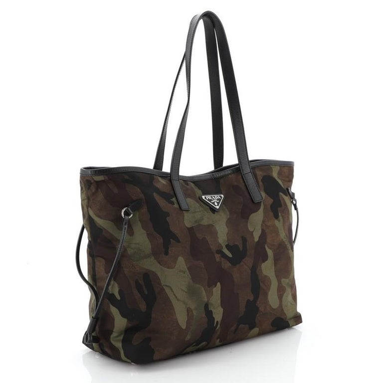 This Prada Camouflage Convertible Open Tote Tessuto Medium, crafted from brown and green camouflage tessuto, features dual leather handles, leather trim and silver-tone hardware. Its magnetic snap closure opens to a black fabric interior with side
