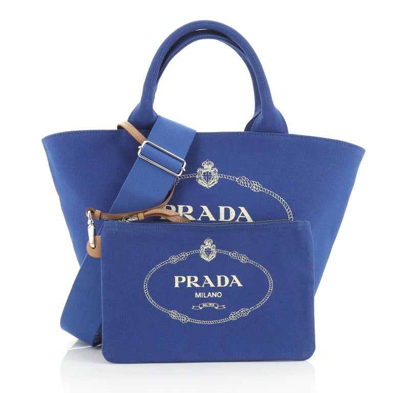 This Prada Canapa Convertible Shopping Tote Canvas Medium, crafted in blue canvas, features dual top handles and silver-tone hardware. It opens to a blue canvas interior with side zip pocket.   Estimated Retail Price: $1,150 Condition: Excellent.