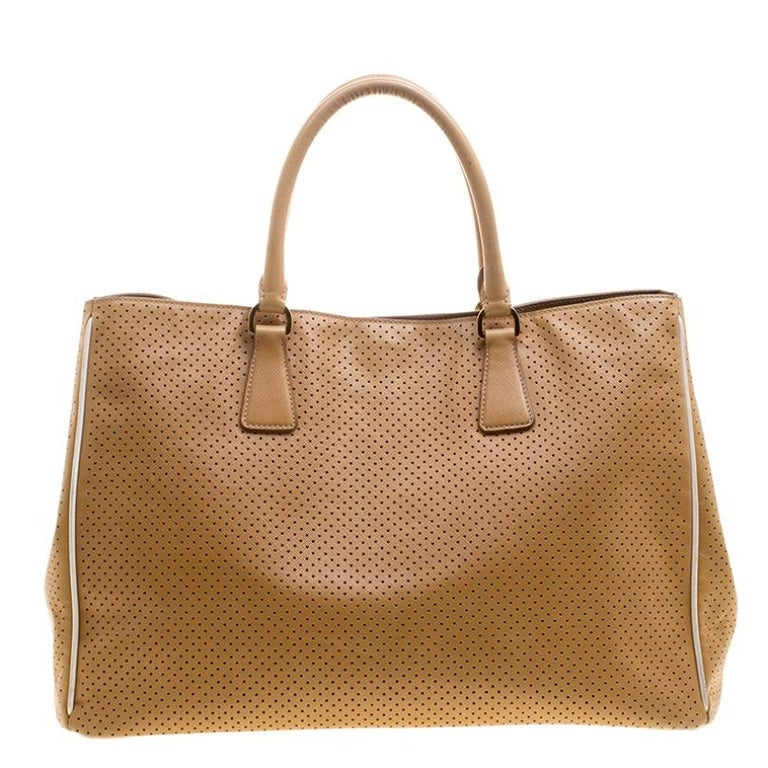 High on appeal and style, this Gardener's tote is a Prada creation. It has been crafted from perforated Saffiano lux leather and shaped to exude class and luxury. The bag comes with two handles, a spacious nylon interior, and gold-tone hardware.
