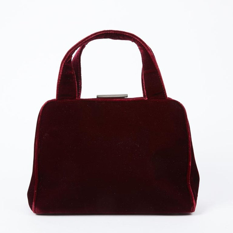 Small Prada red velvet handbag to carry by hand with its double handle. Closing with a rocker button. It is lined in monogram fabric with a zipped pocket. The name