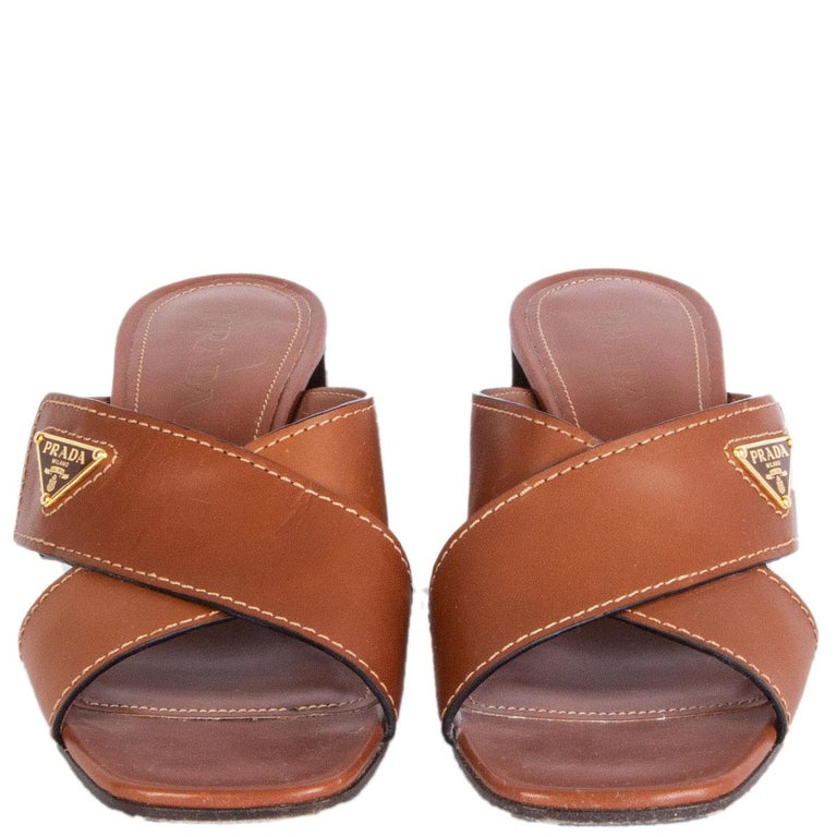 100% authentic Prada criss-cross block-heel mules in brown leather with logo embellishment on the side. Have been worn and are in excellent condition. Come with dust bag.  Measurements Imprinted Size39.5 Shoe Size39.5 Inside Sole25cm