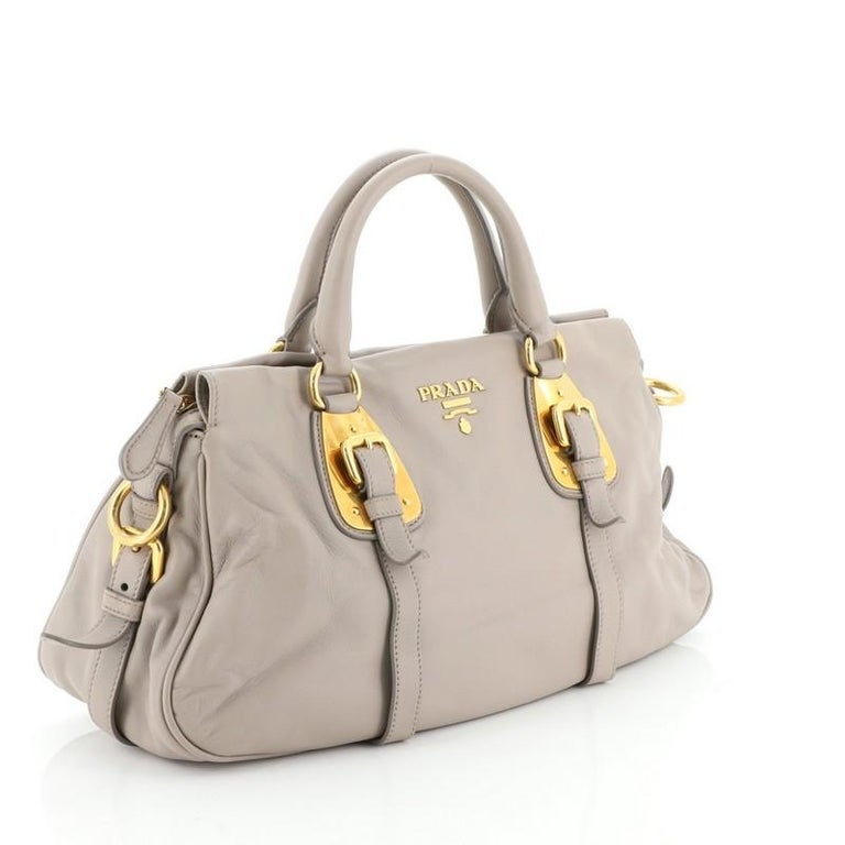 This Prada Convertible Belted Satchel Soft Calfskin Medium, crafted from neutral soft calfskin leather, features belted sides and front, dual rolled leather handles, Prada Milano logo, and gold-tone hardware. Its top zip closure opens to a neutral