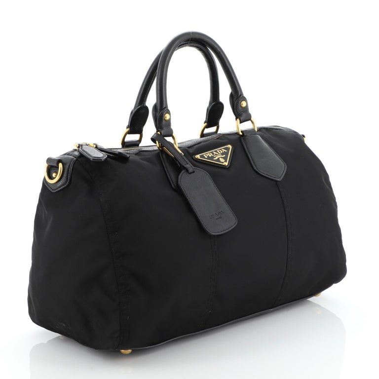 This Prada Convertible Boston Bag Tessuto Large, crafted from black tessuto, features dual rolled leather handles, signature Prada logo and gold-tone hardware. Its zip closure opens to a black fabric interior.   Condition: Very good. Odor in