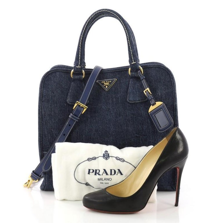 This Prada Convertible Open Tote Denim Medium, crafted in blue denim, features a raised Prada logo at the center, dual rolled leather handles, and gold-tone hardware. Its snap button closure opens to an orange and white fabric interior with side zip