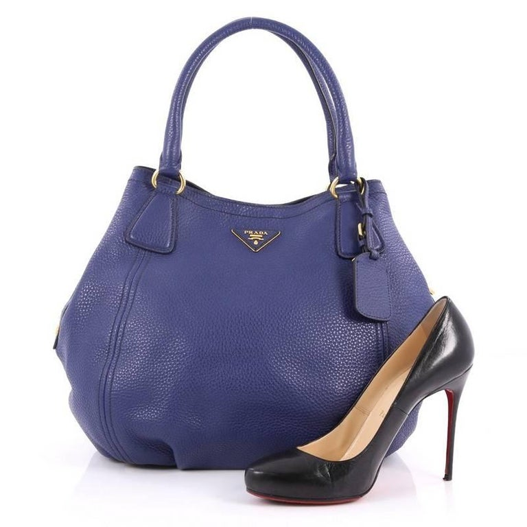 This authentic Prada Convertible Satchel Vitello Daino Medium is elegant in its simplicity and structure. Crafted from blue vitello daino leather, this tote features dual-rolled leather handles, raised Prada logo, side button snaps, protective base