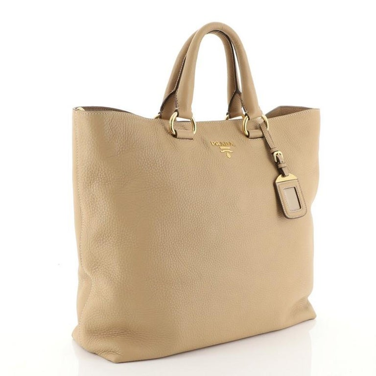 This Prada Convertible Shopper Tote Vitello Daino Large, crafted from neutral vitello daino leather, features dual rolled leather handles, raised Prada logo at the center, and gold-tone hardware. Its magnetic snap closure opens to a neutral fabric