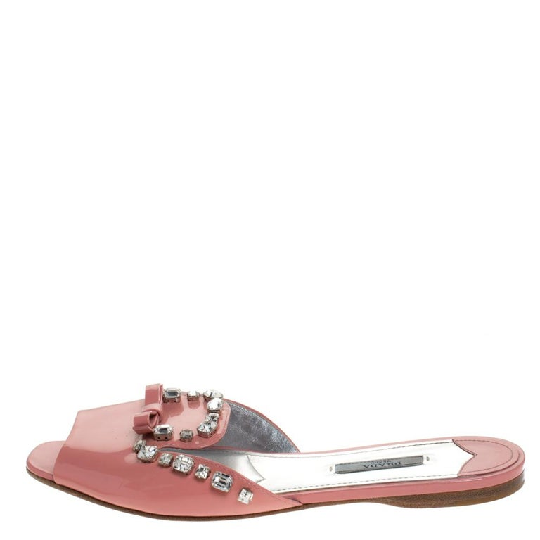Amp up your casual style with these stunning flat slides from the house of Prada. Crafted in Italy, they are made from patent leather. They come in a pretty coral pink shade and are styled with open toes, broad vamp straps embellished with a bow and