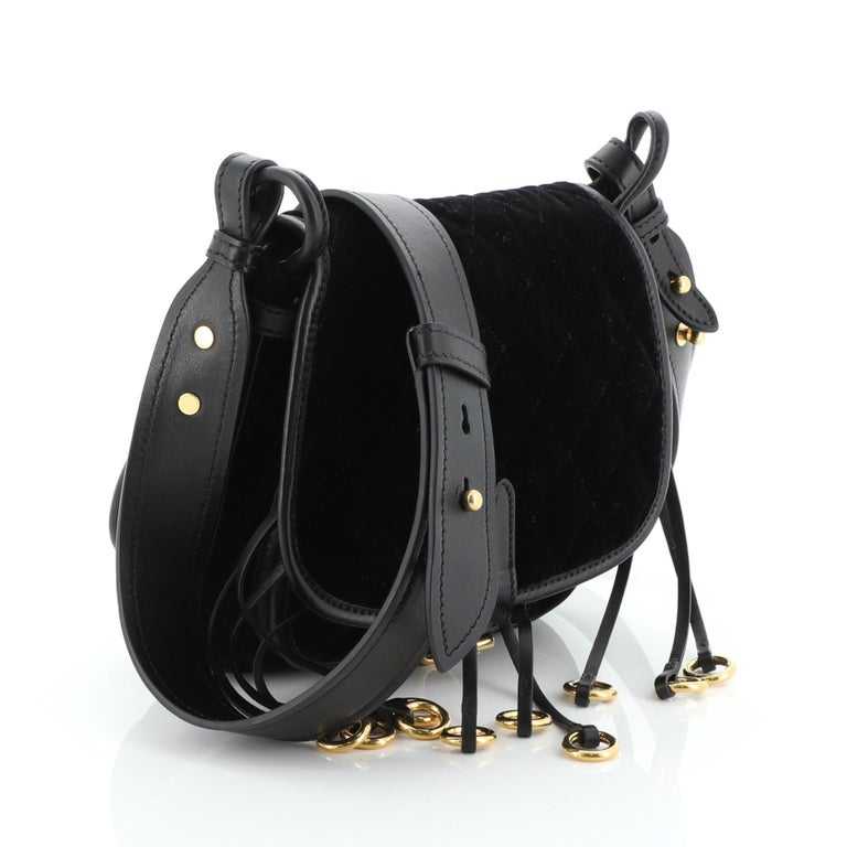 This Prada Corsaire Shoulder Bag Quilted Velvet with Calfskin Small, crafted from black velvet with calfskin leather, features an adjustable shoulder strap, leather fringe with metal rings, frontal flap, and gold-tone hardware. Its buckle closure