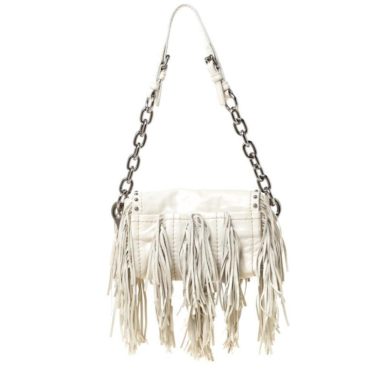 You will love carrying this stunning bag from Prada that is sure to grab you a lot of compliments. The cream bag is crafted from leather and features a chic silhouette. It flaunts fringe detailing on the exterior and comes with a push lock front