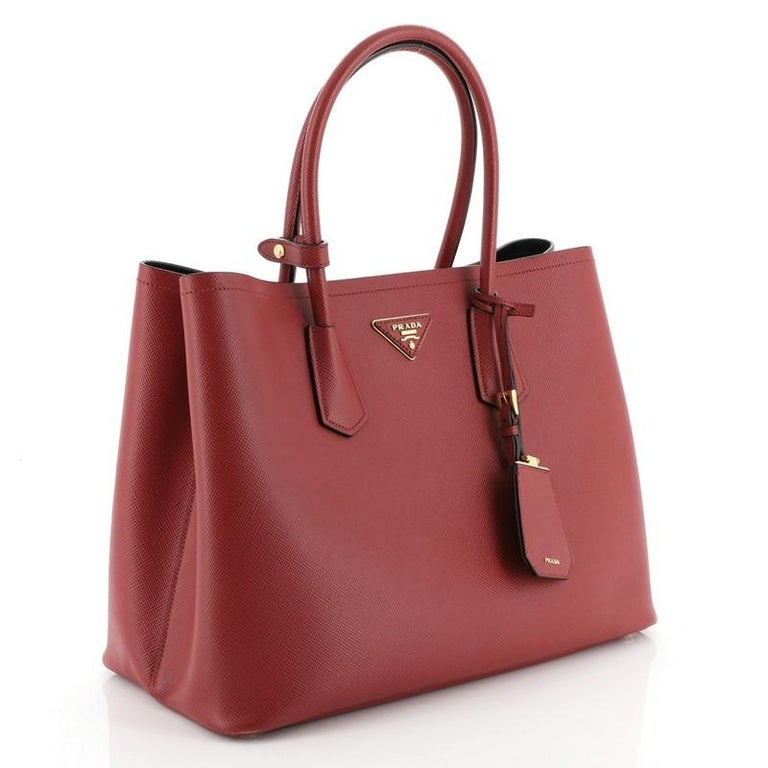 This Prada Cuir Double Tote Saffiano Leather Large, crafted from red saffiano leather, features dual rolled handles, triangle logo at the center, and gold-tone hardware. It opens to a black leather interior with middle flap compartment.   Estimated