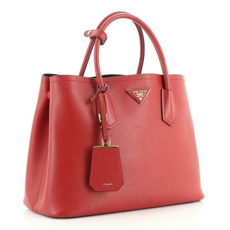This Prada Cuir Double Tote Saffiano Leather Medium, crafted from red saffiano leather, features dual rolled handles, triangle logo at the center, and gold-tone hardware. It opens to a black leather interior with middle flap compartment.   Estimated