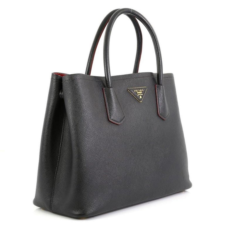 This Prada Cuir Double Tote Saffiano Leather Small, crafted from black saffiano leather, features dual rolled handles, triangle logo at the center, and gold-tone hardware. It opens to a black and red leather interior with middle flap compartment.