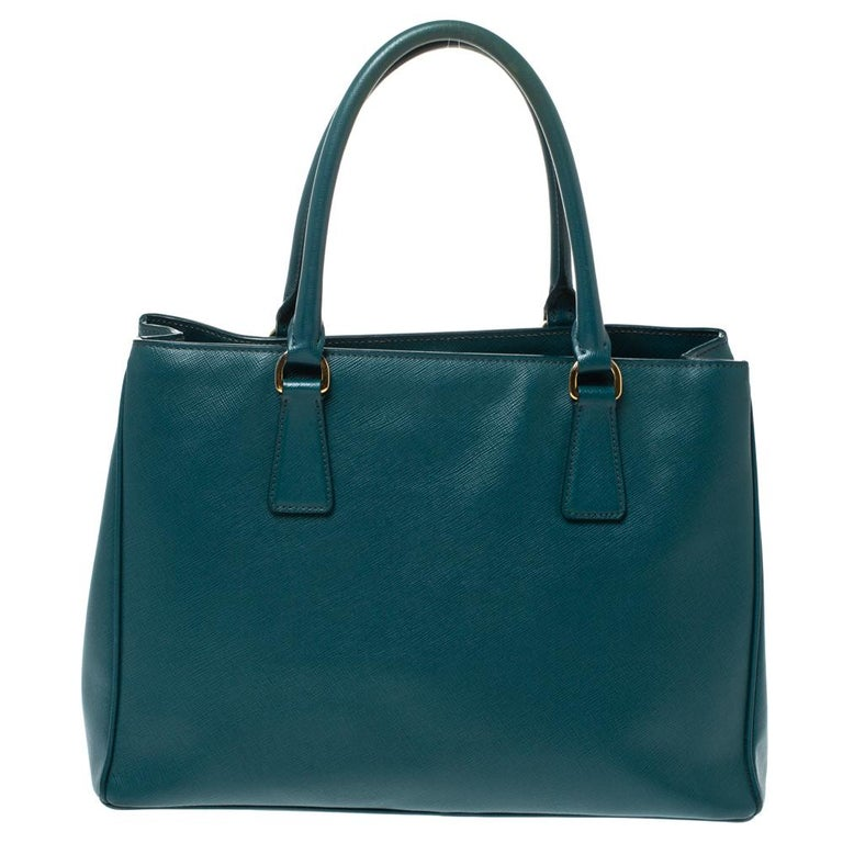 Loved for its classic appeal and funtional design, Galleria is one of the most iconic and popular bags from the house of Prada. This beauty in green is crafted from leather and is equipped with two top handles, the brand logo at the front and a